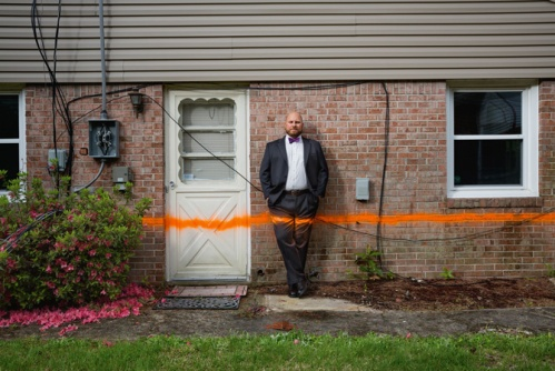 "An orange line sprayed on this condemned house—and on Robb Braidwood of the Chesapeake, Virginia, Office of Emergency Management—marks the typical flood height in the neighborhood. ""It doesn't take a major storm,"" says Braidwood. ""Heavy rain and the right wind during a high tide will do it."""